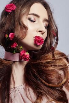 Mulher bonita com flores rosas em cabelos longos