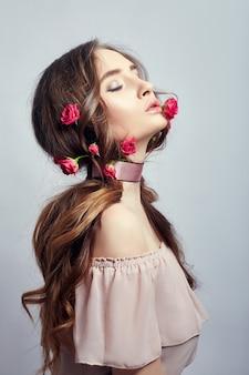 Mulher bonita com flores rosas em seus longos cabelos, uma bandagem em volta do pescoço. limpe a linda pele do rosto