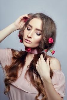 Mulher bonita com flores rosas em seus longos cabelos