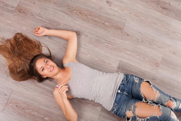 Mulher bonita com fones de ouvido deitado no chão