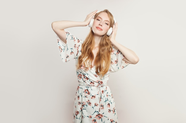 Mulher bonita com fones de ouvido. modelo ruiva ouvindo música em branco