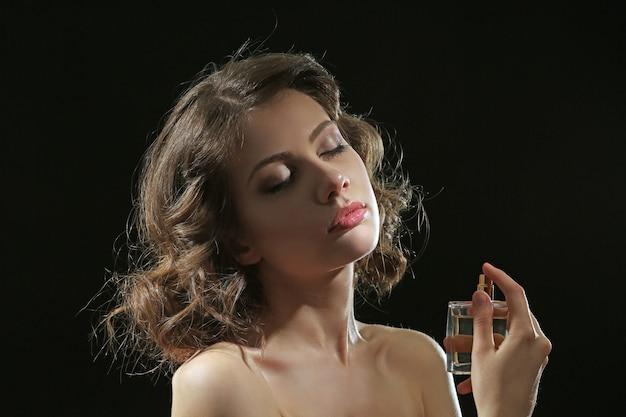 Mulher bonita com frasco de perfume