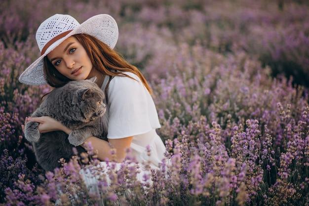 Mulher bonita com gato em um campo de lavanda