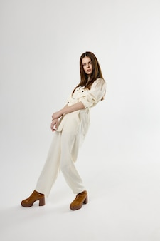 Mulher bonita com glamour da moda de macacão branco