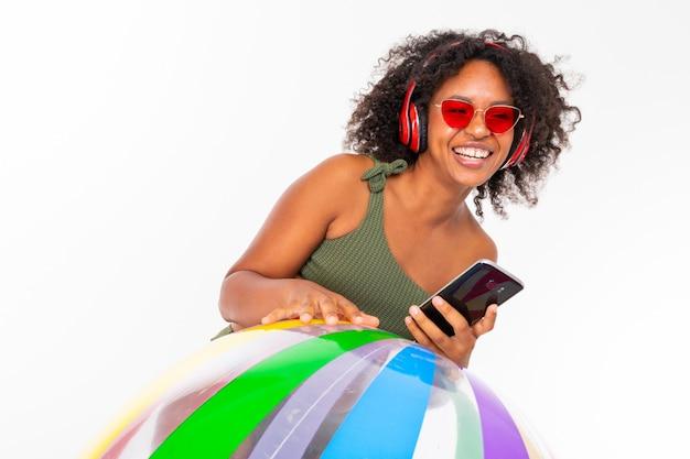 Mulher bonita com grandes fones de ouvido vermelhos, óculos escuros e telefone fica com bola de borracha grande isolada no fundo branco