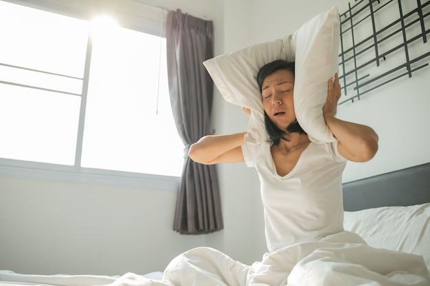 Mulher bonita com gritos enquanto está sentado na cama. mulher jovem cobre os ouvidos com um travesseiro. dor de cabeça por barulho. mulher adulta irritada, sofrendo de barulho de vizinho.