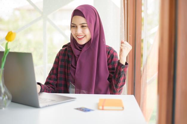 Mulher bonita com hijab na mesa dela