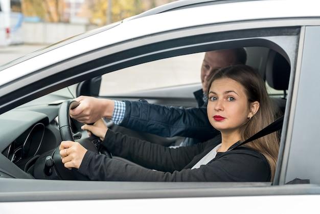 Mulher bonita com instrutor sentado no carro