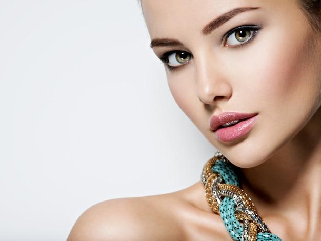 Mulher bonita com joias de maquiagem à noite e foto de moda beleza