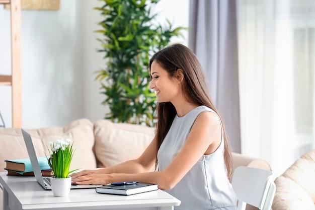 Mulher bonita com laptop moderno sentada à mesa na sala