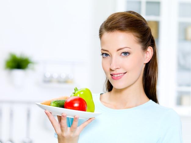 Mulher bonita com legumes em um prato na cozinha