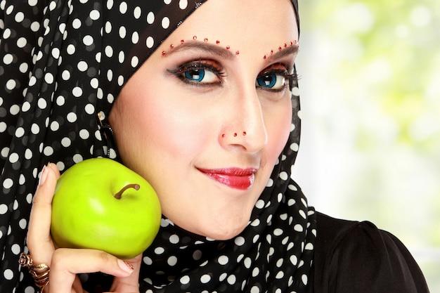 Mulher bonita com lenço preto segurando a maçã verde