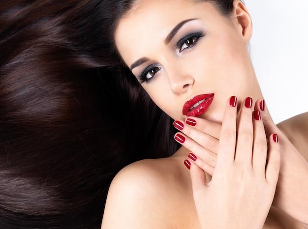 Mulher bonita com longos cabelos castanhos lisos e elegantes unhas vermelhas