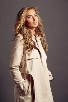 Mulher bonita, com longos cabelos loiros com casaco de pele bege