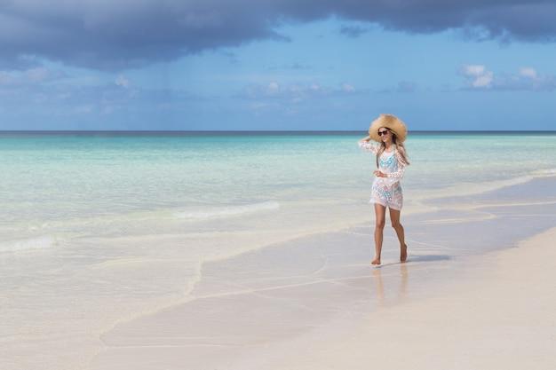 Mulher bonita com longos cabelos loiros em biquíni azul correndo na praia tropical com areia branca