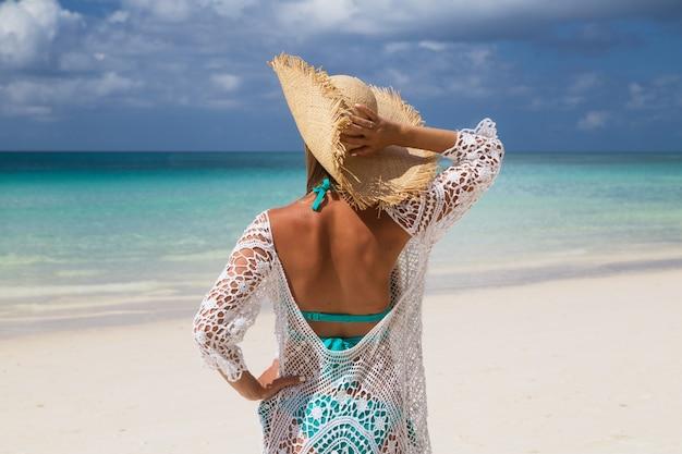 Mulher bonita com longos cabelos loiros em biquíni azul na praia tropical com areia branca