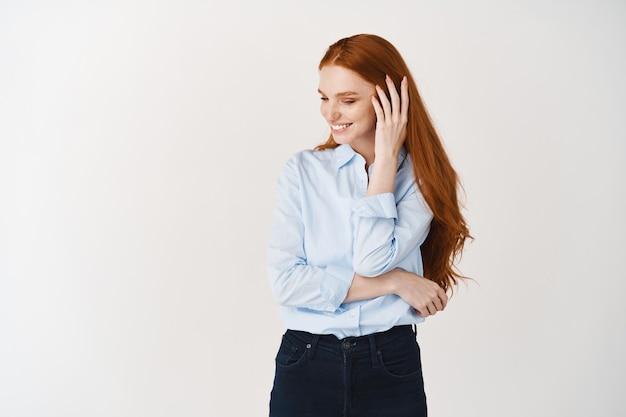 Mulher bonita com longos cabelos ruivos corando e olhando para longe tímida, em pé sobre uma parede branca e sorrindo