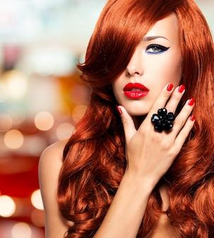 Mulher bonita com longos cabelos vermelhos com lábios brilhantes sensuais e unhas vermelhas.