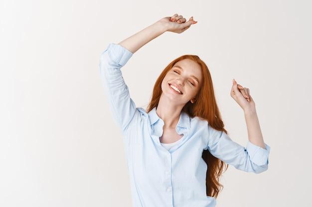 Mulher bonita com longos cabelos vermelhos estalar os dedos e dançar, curtindo ouvir música, encostada em uma parede branca