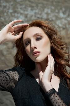 Mulher bonita com longos cabelos vermelhos posando na natureza