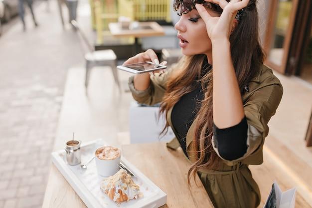 Mulher bonita com longos cílios pretos tirando foto do almoço em um café