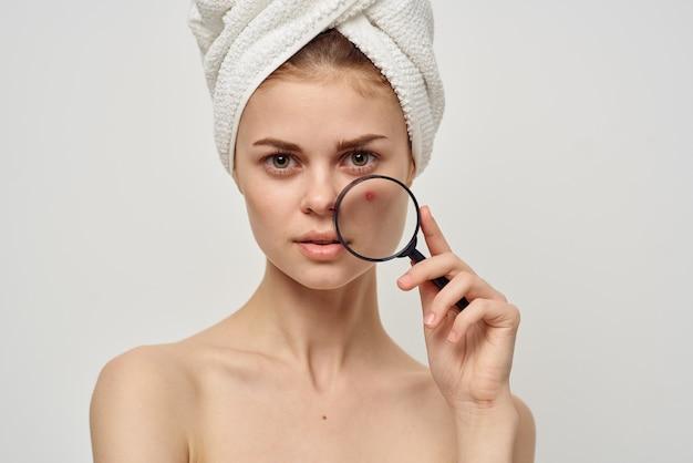Mulher bonita com lupa perto da aparência do rosto acne acne cuidados da pele.