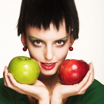 Mulher bonita com maçãs isoladas no branco