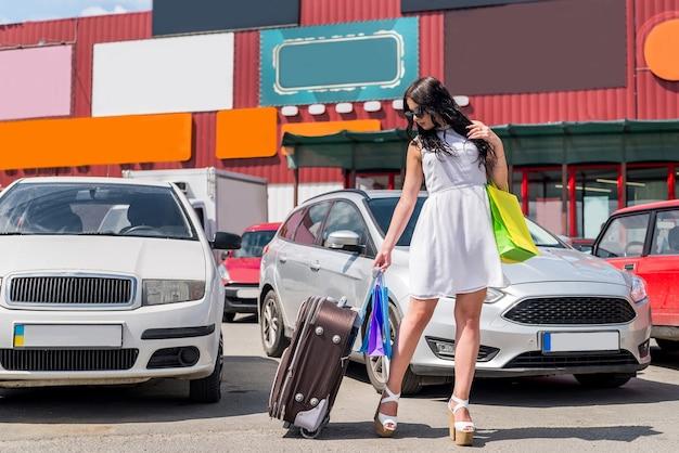 Mulher bonita com mala e sacolas de compras perto do carro