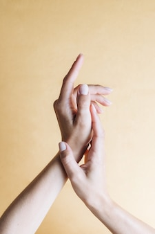 Mulher bonita com mãos femininas de beleza com manicure francesa e pele macia sobre fundo bege