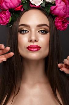 Mulher bonita com maquiagem brilhante e flores na cabeça