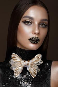 Mulher bonita com maquiagem criativa de arte preta e acessórios de ouro