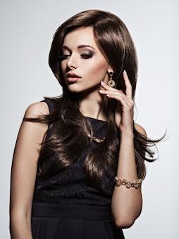 Mulher bonita com maquiagem de noite e joias de ouro