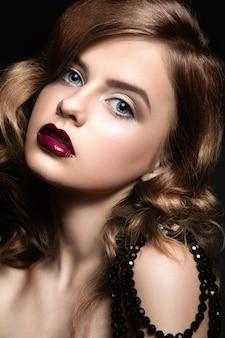 Mulher bonita com maquiagem de noite, lábios vermelhos e cachos.
