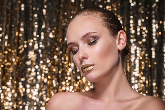 Mulher bonita com maquiagem dourada