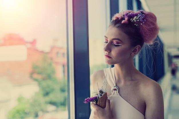 Mulher bonita com maquiagem fresca se passando perto de uma janela com flores
