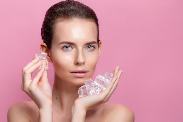 Mulher bonita com maquiagem natural segurando cubos de gelo perto do rosto