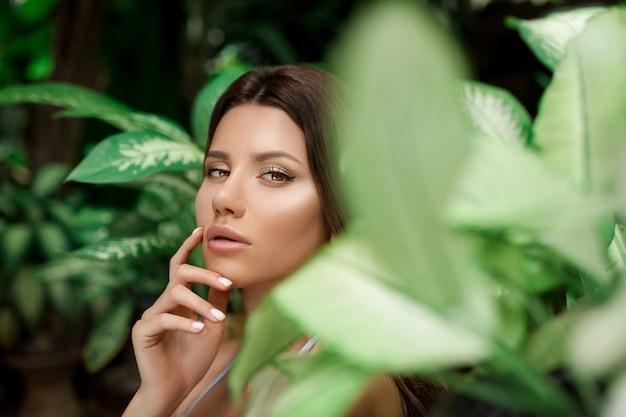 Mulher bonita com maquiagem nos trópicos de arbustos folhas close-up