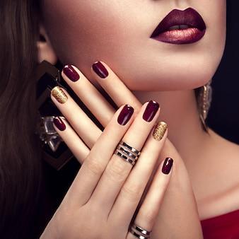 Mulher bonita com maquiagem perfeita e borgonha e manicure dourado