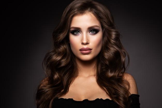 Mulher bonita com maquiagem profissional e cabelos cacheados