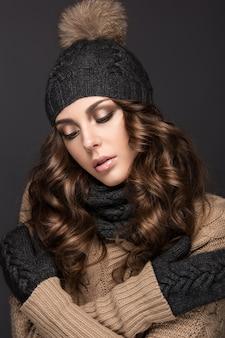Mulher bonita com maquiagem smokey, cachos no chapéu de malha preto