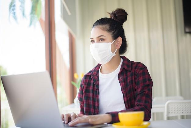 Mulher bonita com máscara está trabalhando no computador laptop na cafeteria