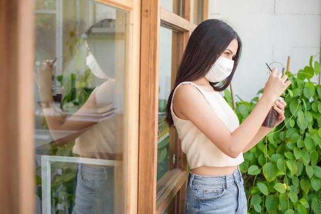Mulher bonita com máscara facial está segurando café na frente da cafeteria