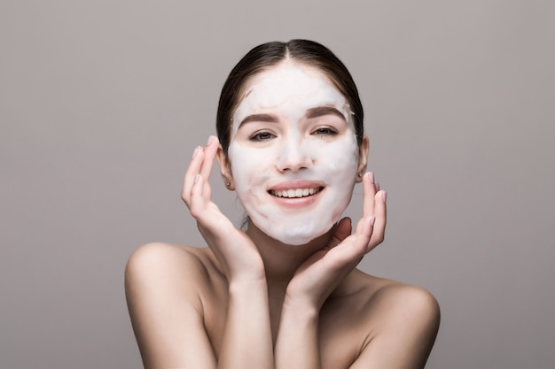 Mulher bonita com máscara facial na parede branca. cosméticos, cuidados com a pele.