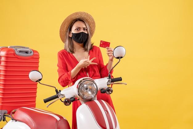 Mulher bonita com máscara preta segurando um cartão de crédito perto de motocicleta