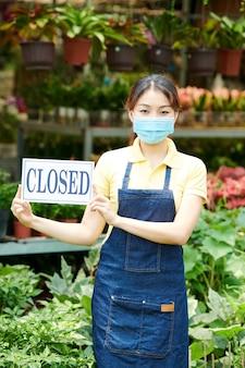 Mulher bonita com máscara protetora fechando centro de jardinagem ou viveiro de plantas devido à pandemia de coronavírus