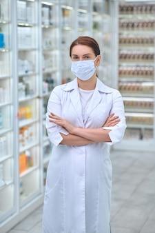 Mulher bonita com máscara protetora na farmácia