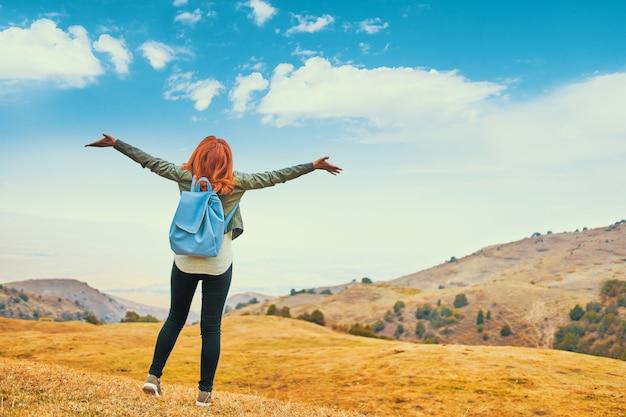 Mulher bonita com mochila azul ao ar livre apreciando montanhas de natureza