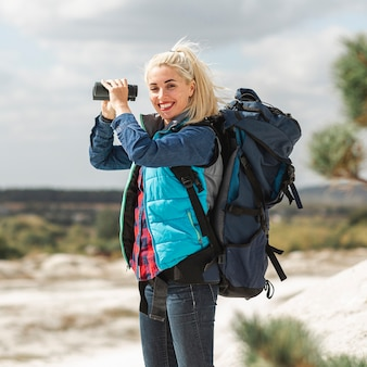 Mulher bonita com mochila e binóculos