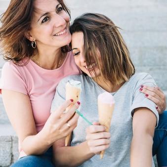 Mulher bonita com mulher abraçando de sorvete