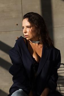 Mulher bonita com o cabelo molhado posando no estúdio, vestindo um blazer preto enorme e um colar brilhante